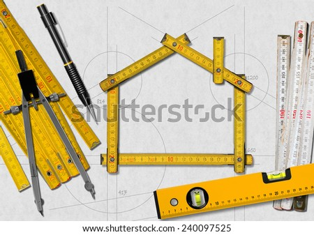 House project concept. Wooden meter ruler in the shape of house with a pencil, drawing compass, two meter tools and spirit level on a white paper - stock photo