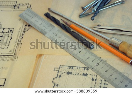 house remodel, design project on an old paper  with office tools and consruction tools., Construction instruments, for the design of the house, screwdriver, ruler, nails, screws.  - stock photo