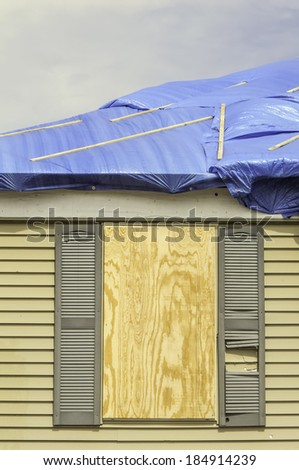 House repairs after tornado: Boarded window beneath roof with protective sheets of blue plastic - stock photo