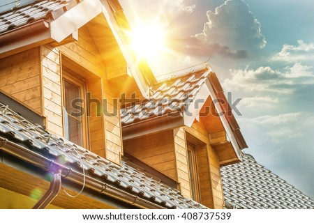 House Roof and Attic Windows Closeup. Sunny Day. Housing and Construction Concept Photo. - stock photo