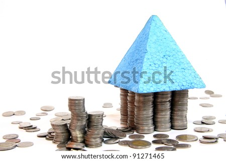 House roof built on top of coins depicting concept of house loan debt/buying house/house mortgage/house value/sub-prime crisis on white background - stock photo
