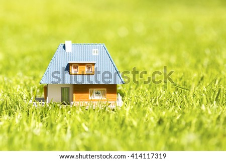 house scale model on green grass with copy space - stock photo