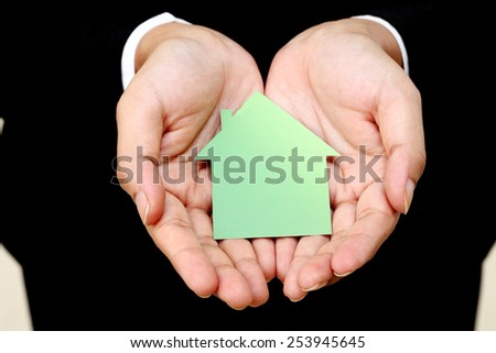 House shape in business woman's hands - stock photo
