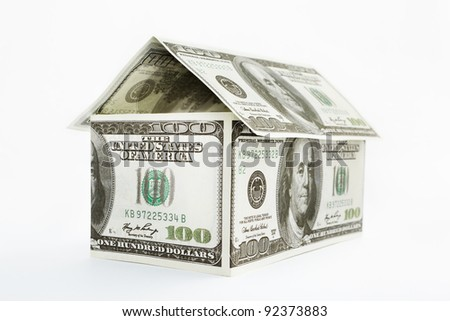 House shape made from 100 dollar bills over white background