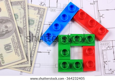 House shape of colorful building blocks and banknotes lying on construction drawing of house, concept of building house, drawings for projects - stock photo