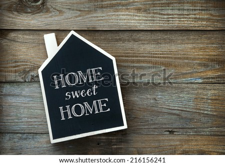House Shaped Chalkboard sign  on rustic wood Home Sweet Home - stock photo
