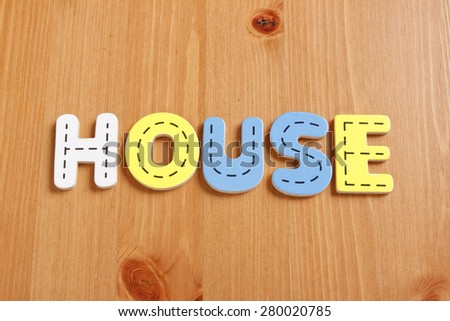 HOUSE, spell by woody puzzle letters with woody background - stock photo