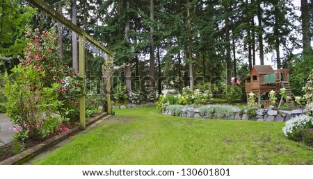 House spring backyard with roses patio and kids playground with wooden swing and slide. - stock photo
