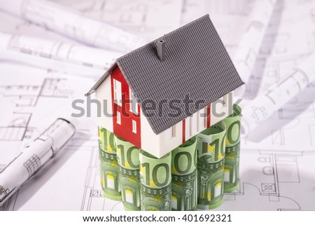 House stands on one hundred euro banknotes, surrounded by blueprints. - stock photo