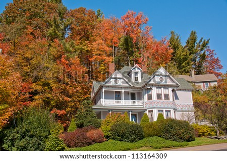 House surrounded by Fall foliage, Blowing rock, N.C. A gingerbread house in North Carolina nestles amongst colorful autumn foliage - stock photo