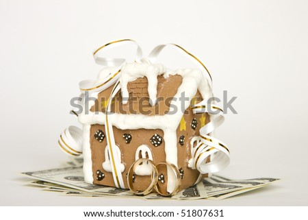 House tied with ribbon and money, and wedding rings - stock photo