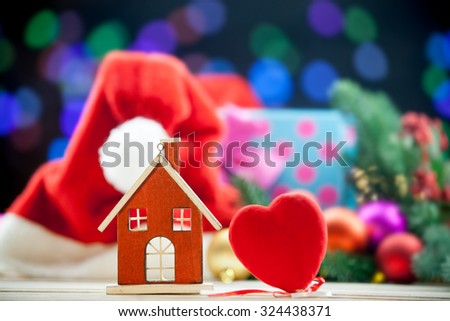 House toy and heart shape toy on Christmas background.