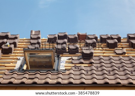 House under construction. Roofing tiles with open skylight - stock photo