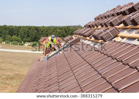 House under construction. Roofing tiles with open skylights. A worker installs skylights. - stock photo