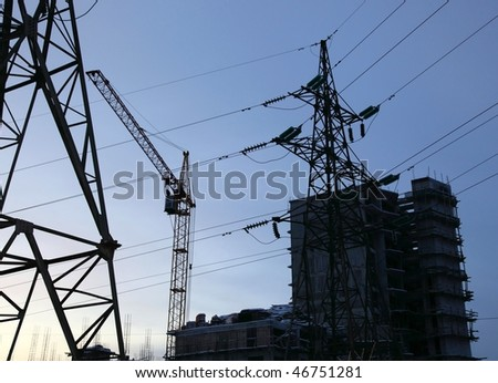 House under construction. Two electricity pylons. Twilight.