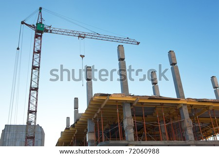 House under construction with a tower crane - stock photo