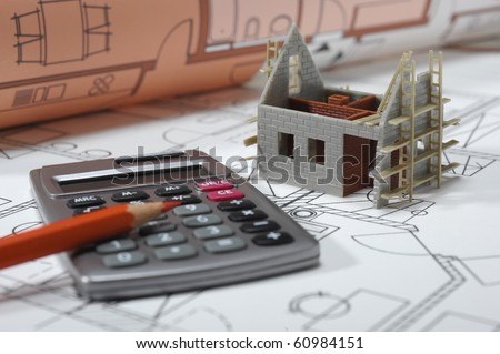house under construction with blue print and calculator - stock photo