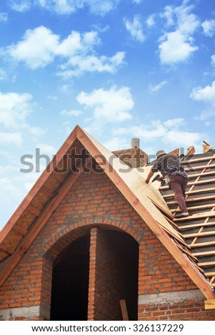 House under construction. Workers installing fibreboard on the roof - stock photo