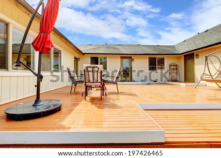 House walkout deck with patio table set and red umbrella - stock photo