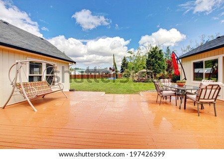 House walkout deck with patio table set and swing. - stock photo