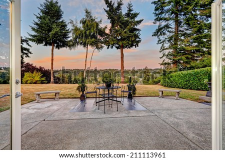 House walkout deck with patio table, stone benches overlooking scenic backyard view during sunset - stock photo