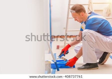 House Walls Painting. Young Caucasian Men Painting His Home. Construction and Renovation. - stock photo