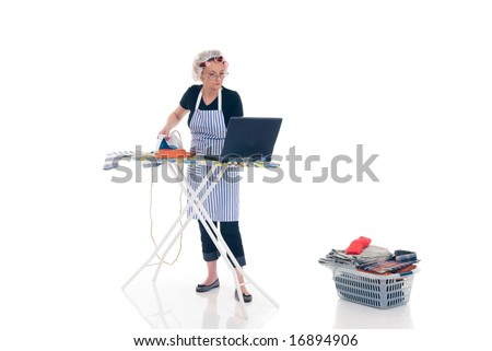 House wife, basket with ironed goods,  daily household, chatting on laptop. - stock photo