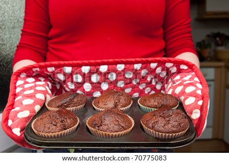 House wife presenting freshly baked chocolate muffins - stock photo