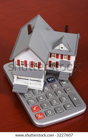 House with a calculator - calculating housing costs - stock photo