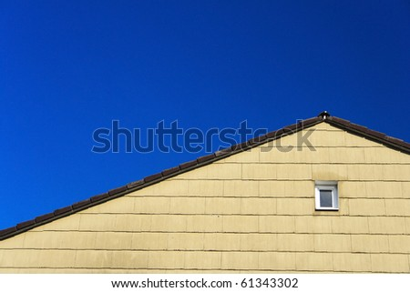 House with a small window and blue sky - stock photo
