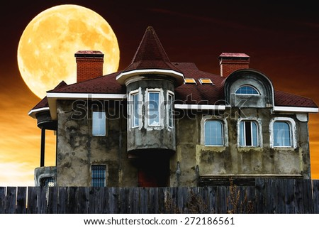 house with a tower tube night against the sky and a large moon - stock photo