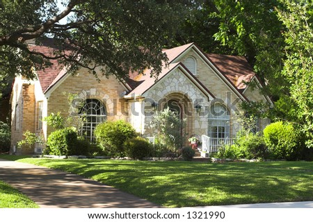 house with beautiful mixture of light colored and white stone and brick; arched windows and entryway; surrounded by green foliage - stock photo