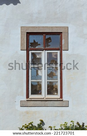 House with broken glass window - stock photo