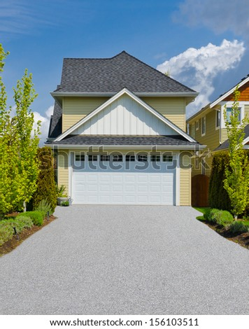 House with double doors garage and long driveway. North America. - stock photo