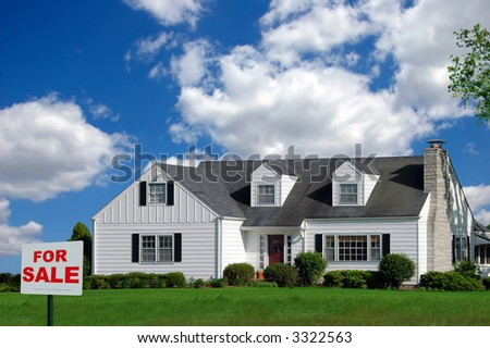 House with For Sale sign in the front yard over a colorful sky with clouds. - stock photo