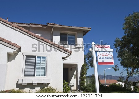 House with foreclosure sign against blue sky - stock photo