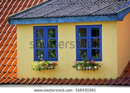 House with loft apartment and two windows with blue frames and window boxes with flowers. - stock photo