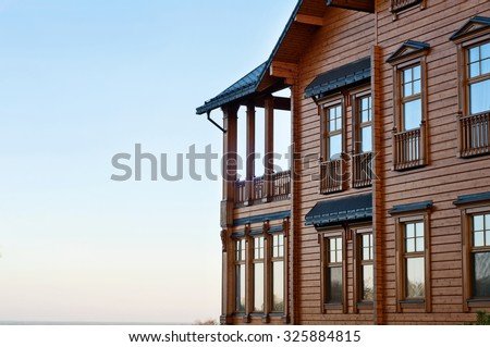 House with log. The facade of elite houses of wood against blue sky background - stock photo