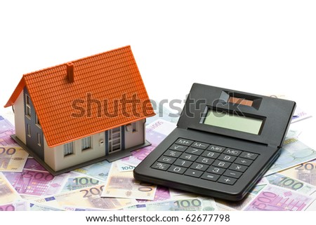 House with money and calculator over white background - mortgaging concept
