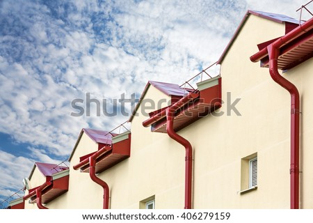 house with new red tiled roof and gutter under cloudy sky - stock photo