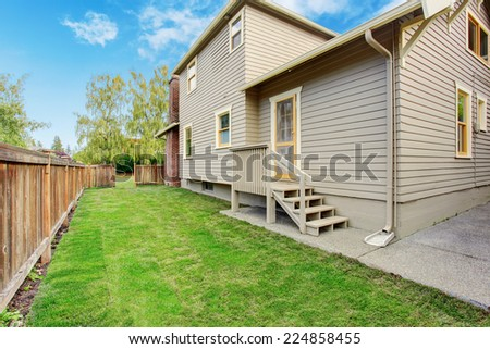House with small deck and fenced backyard - stock photo