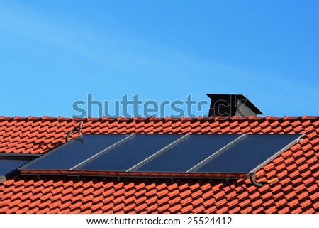 House with solar heating system on the roof. - stock photo