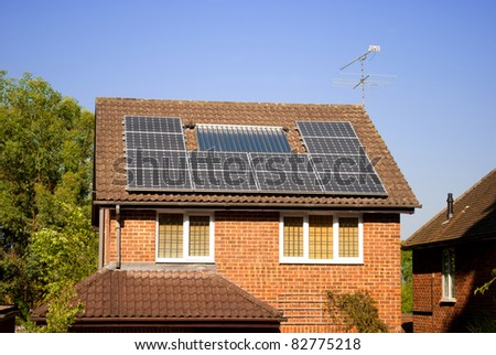 House with solar panels on roof, electricity generation - stock photo