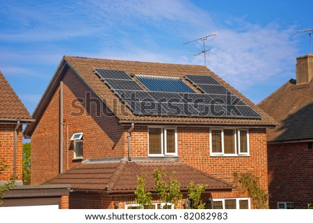 House with solar panels on roof - regenerative energy system electricity generation - stock photo