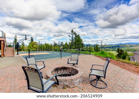 House with sport court and patio area. View of fire pit with chairs - stock photo