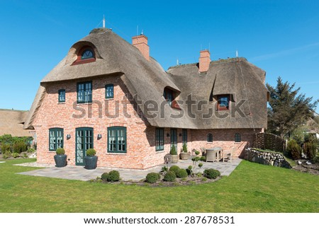 House with thatched roof in front of blue sky - stock photo