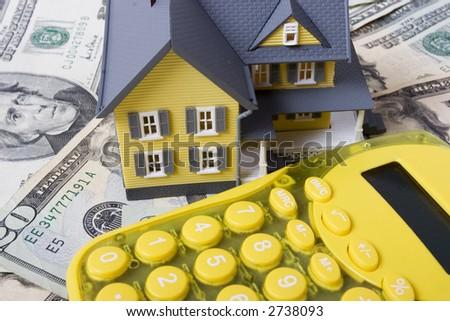 House with twenty dollar bills background and calculator - stock photo