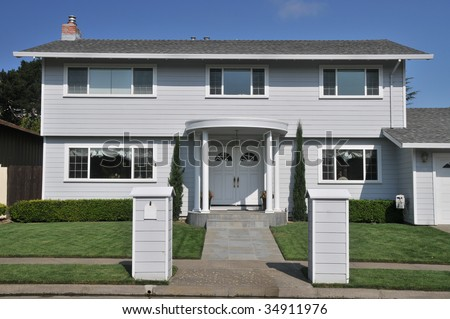 House with two structures, one a mailbox, columns - stock photo