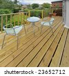 house with wooden decking and patio leading to garden - stock photo