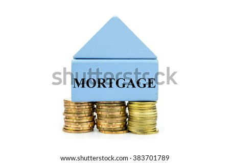 House Wooden Block and stacked of Coins with word Mortgage written - stock photo